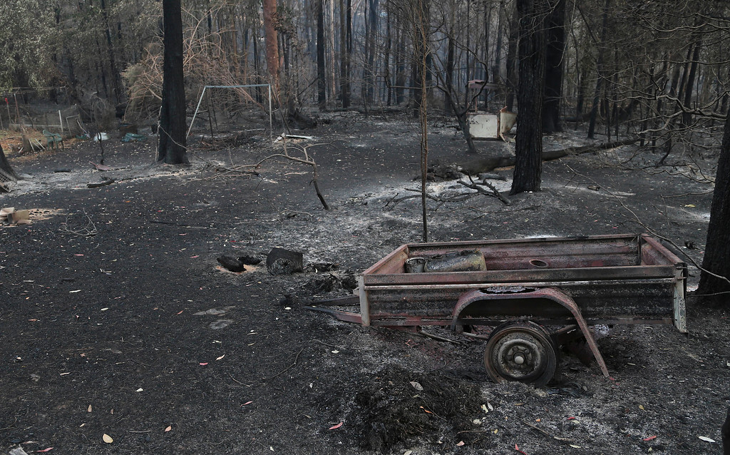 . A burnt trailer sits in the back yard of destroyed homes in Sunny Ridge Drive in Winmalee 65 kilometers (40 miles) from Sydney in  Australia,  Tuesday, Oct. 22, 2013 after a wildfire swept through the street burning several homes on Oct 18, 2013. (AP Photo/Rob Griffith)