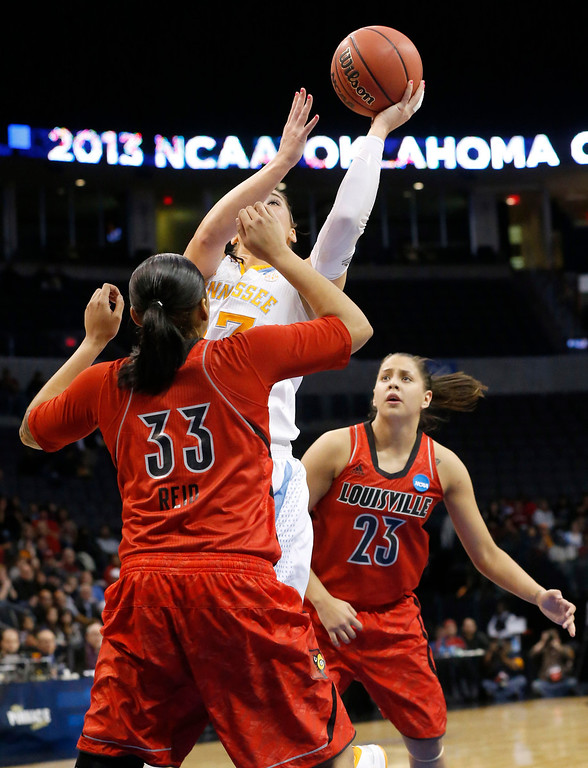 . Tennessee forward Taber Spani (13) shoots between Louisville forward Monique Reid (33) and guard Shoni Schimmel (23) in the first half of the regional final in the NCAA women\'s college basketball tournament in Oklahoma City, Tuesday, April 2, 2013. Louisville won 86-78. (AP Photo/Sue Ogrocki)