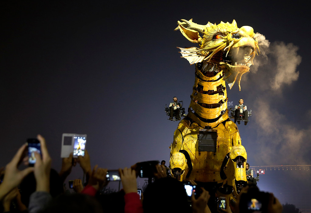 """. People use smartphones to take photos of the French production company La Machine\'s latest creation \""""the Long Ma\"""" or Dragon Horse performs in front of the Bird\'s Nest Stadium in Beijing, China Sunday, Oct. 19, 2014. The performance, which attended by French Foreign Minister Laurent Fabius and his Chinese counterpart Wang Yi, mark the climax of celebrations for the 50th anniversary of Sino-French diplomatic relations. (AP Photo/Andy Wong)"""