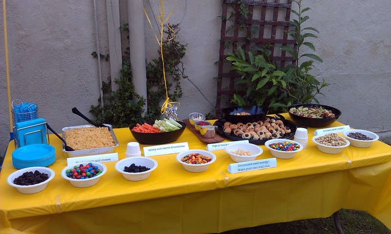 Party food includes monkey-roni and cheese (in wheat and gluten-free varieties); celery and carrot drumsticks; pigs in blankets (in vegetarian and vegan varieties); avocado salad; and make-your-own trail mix