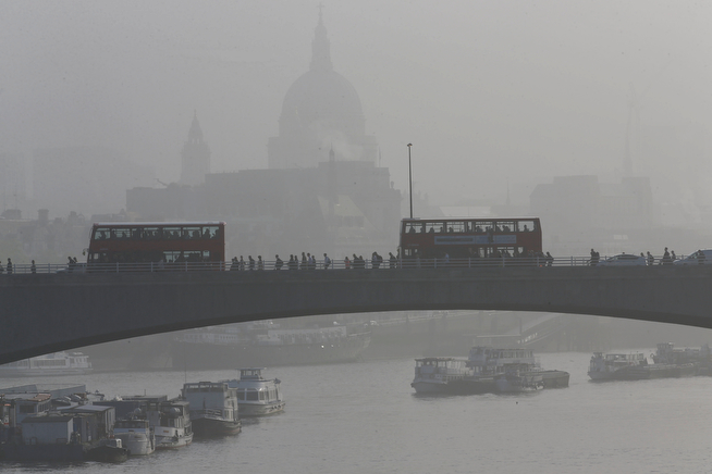 . St Paul\'s Cathedral is covered in mist as people and buses cross Waterloo Bridge during the second day of a 48 hour workers strike partially closing the London Underground train network in London, Wednesday, April 30, 2014. Members of the Rail, Maritime and Transport Union went on strike over management plans to close all ticket offices on the subway network, known as the Tube, which will result in around 750 job losses from the Underground\'s staff of 18,000. A further 72 hour strike is planned starting May 5. (AP Photo/Sang Tan)
