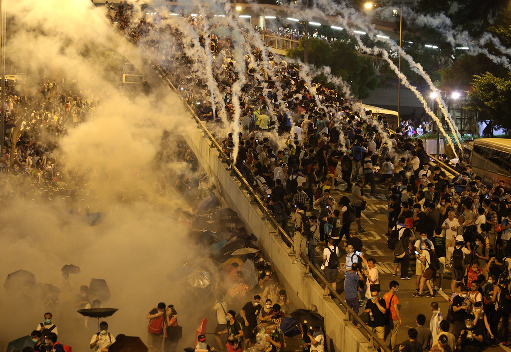 . Police fire tear gas upon pro-democracy demonstrators near the Hong Kong government headquarters on September 28, 2014. Police fired tear gas as tens of thousands of pro-democracy demonstrators brought parts of central Hong Kong to a standstill Sunday, in a dramatic escalation of protests that have gripped the semi-autonomous Chinese city for days. AFP PHOTO / AARON TAM