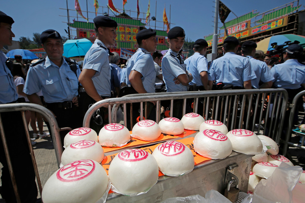 . Police officers look the buns for sale on the outlying Cheung Chau island in Hong Kong to celebrate the Bun Festival Tuesday, May 22, 2018. Thousands of local residents and tourists flocked to an outlying island in Hong Kong to celebrate a local bun festival on Tuesday despite the recording-breaking heat.  The festival features a parade with children dressed as deities floated on poles. Later on Tuesday, contestants will take part in bun-scrambling competition. They will race up a 14-meter bamboo tower to snatch as many plastics buns as possible. Buns that are higher up are worth more points.  (AP Photo/Kin Cheung)