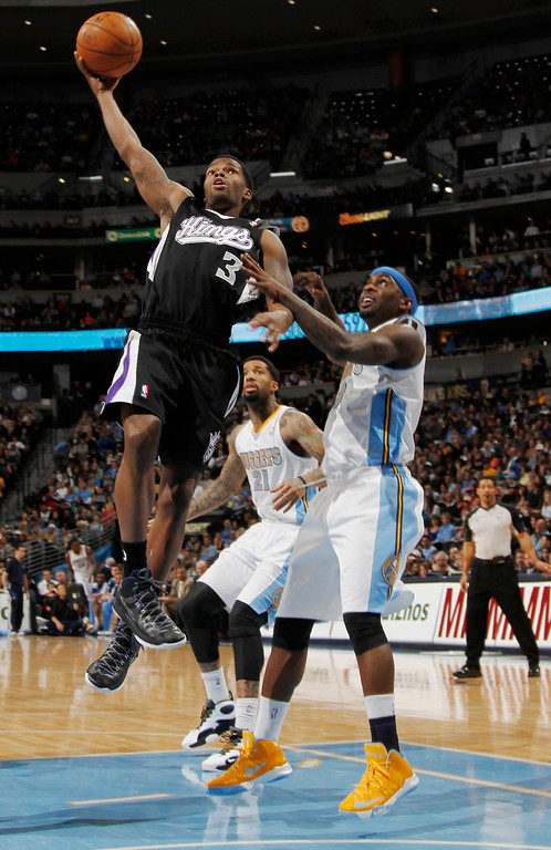 . Sacramento Kings guard Aaron Brooks, left, drives the lane for a shot past Denver Nuggets guard Ty Lawson in the first quarter of an NBA basketball game in Denver on Saturday, Jan. 26, 2013. (AP Photo/David Zalubowski)