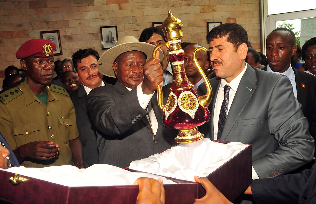 """. Uganda\'s President Yoweri Museveni, center-left, receives a gift from Turkish investors after opening the Galaxy International School Uganda (GISU), outside of Kampala, in Uganda Monday, Feb. 24, 2014. Uganda\'s President Yoweri Museveni on Monday signed into law a new anti-gay bill, with penalties including 14 years in jail for first-time offenders and life imprisonment as the maximum penalty for \""""aggravated homosexuality\"""", saying it is needed to deter what he called the West\'s \""""social imperialism\"""" promoting homosexuality in Africa. (AP Photo/Stephen Wandera)"""