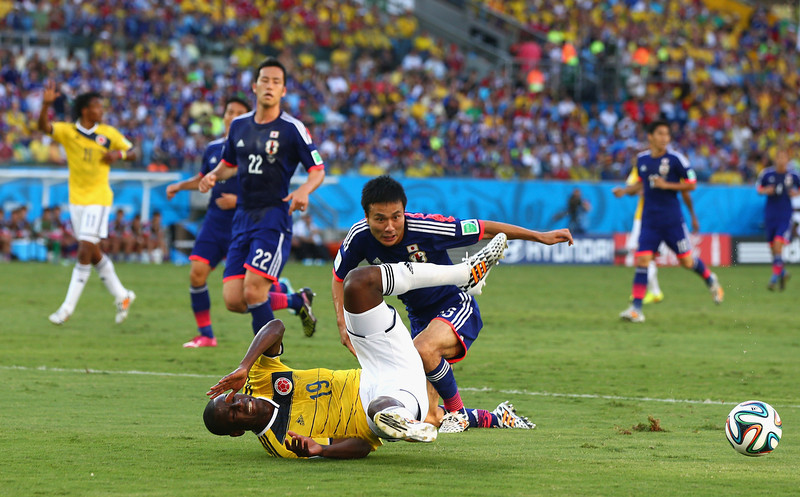 . Yasuyuki Konno of Japan fouls Adrian Ramos of Colombia and concedes a penalty during the 2014 FIFA World Cup Brazil Group C match between Japan and Colombia at Arena Pantanal on June 24, 2014 in Cuiaba, Brazil.  (Photo by Elsa/Getty Images)