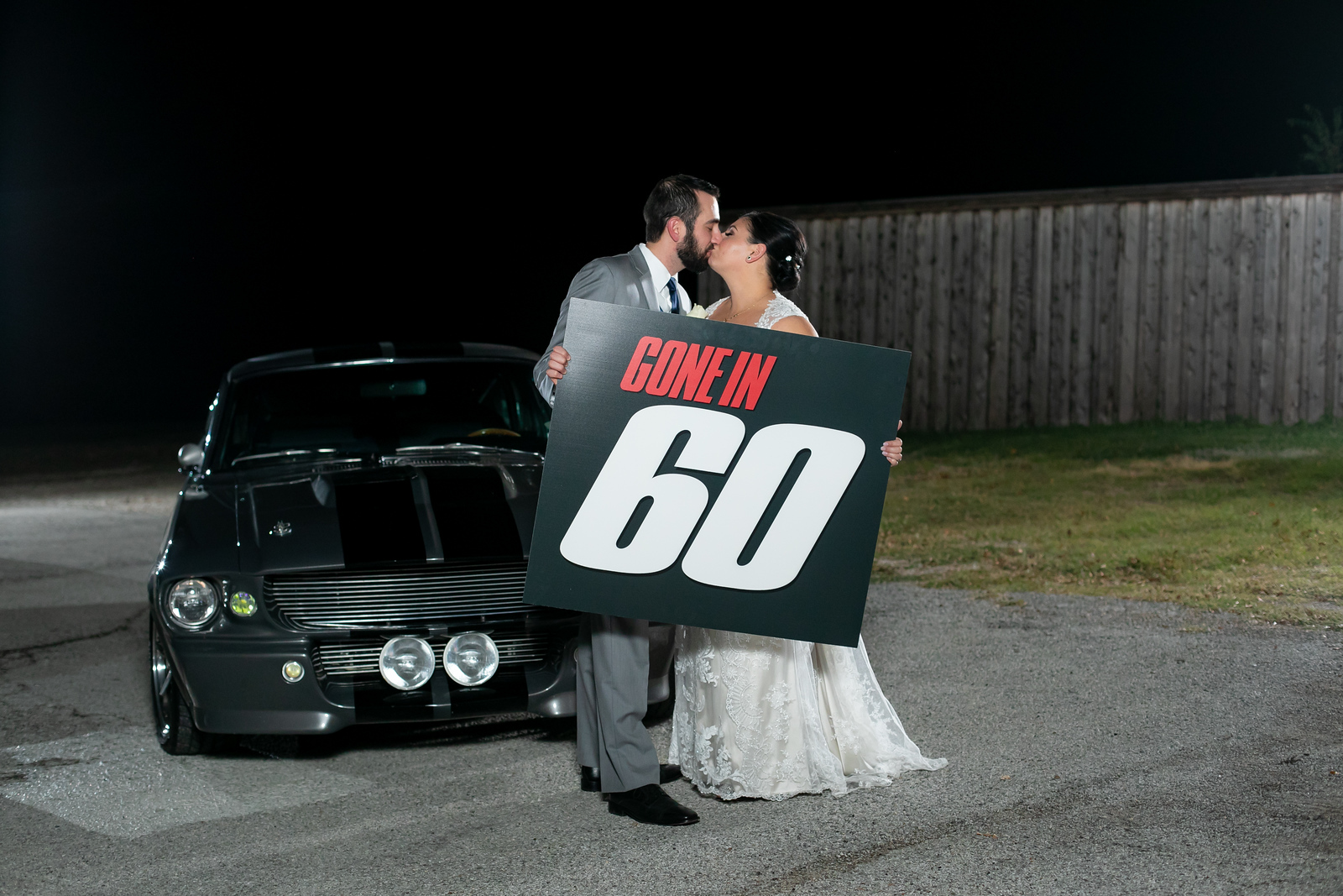 bride and groom holding a gone in 60 seconds sign up next to a classic Mustang GT 500 on their wedding night
