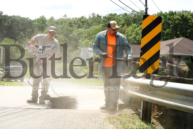Hunter Bartolicius and Damon Hoak of the Butler County bridge work crew perform routine maintainance after inspecting the Muddy Creek Drive bridge over Muddy Creek near Route 8, south of Slippery Rock. Seb Foltz/Butler Eagle 07/25/19