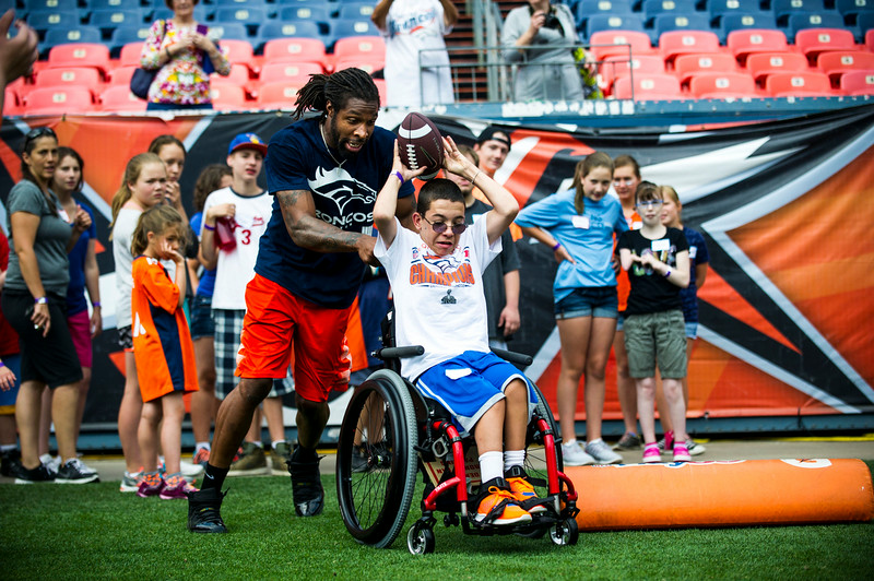 . Patrick McKinney, 15, gets a push from David Bruton #30 of the Denver Broncos during the National Sports Center for the Disableds Denver Bronco\'s Ability Clinic at Sports Authority Field at Mile High on Tuesday, July 08, 2014 in Denver, CO. (Photo by Kent Nishimura/The Denver Post)
