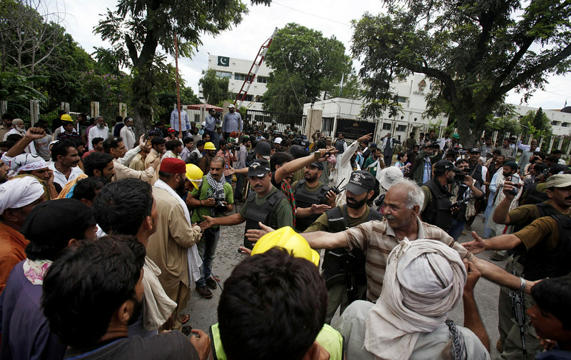 . Pakistani troops push back protesters at the main entry gate of the state television building in Islamabad, Pakistan, Monday, Sept. 1, 2014. Anti-government protesters and Pakistani police have clashed once again as the demonstrators pushed into a sprawling government complex in the country\'s capital in an effort to try to reach the prime minister\'s official residence. (AP Photo/Anjum Naveed)