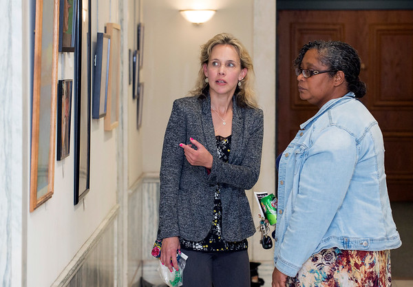 10/09/19 Wesley Bunnell | StaffrrArt work by CSDNB Art Teachers titled Leading by Example IV had its opening reception on Wednesday night at city hall. Kelly Nadolny from Pulaski Middle School, middle, speaks with a fellow teacher.