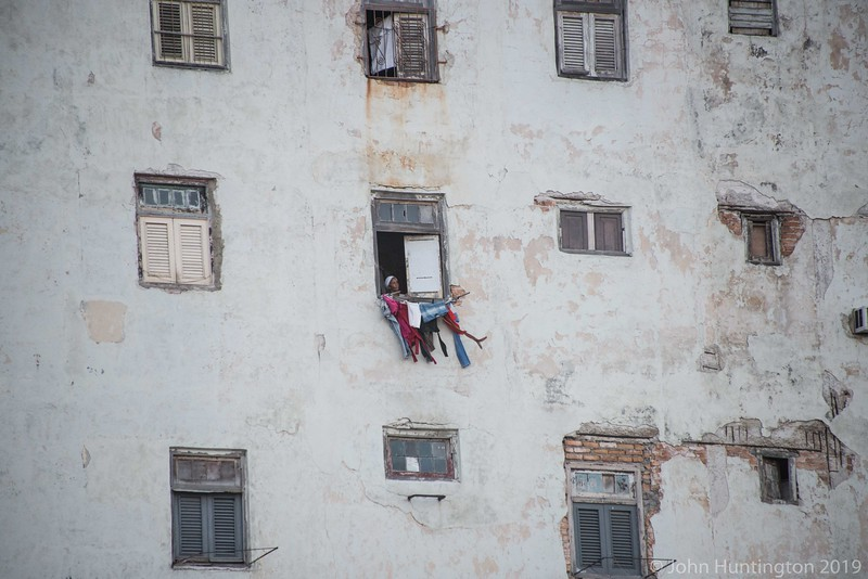HAVANA, CUBA: JANUARY 19, 2014: A woman washes clothes in a window in a decrepit building