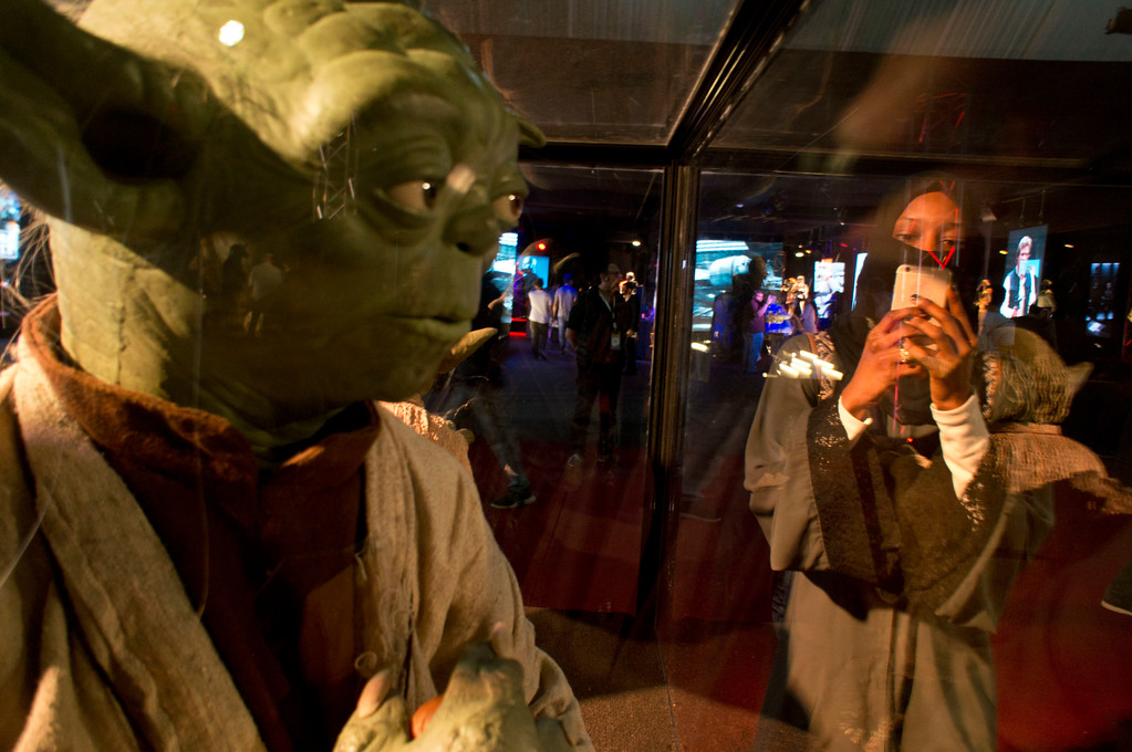 . FILE - In this Friday, Feb. 17, 2017, file photo, a visitor films at the Star Wars exhibition, an American epic space franchise, centered on a film series, during the Saudi Comic Con (SCC) which is the first event of its kind to be held in Jiddah, Saudi Arabia. The kingdom, which bans movie theaters and other entertainment venues, is challenging its ultraconservative image and loosening the reins on fun by opening its doors to live shows, including some American ones. (AP Photo, File)