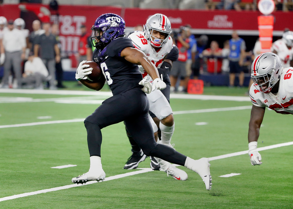 . TCU running back Darius Anderson (6) runs past Ohio State linebacker Malik Harrison (39) and defensive lineman Robert Landers (67) for a long touchdown run during the first half of an NCAA college football game in Arlington, Texas, Saturday, Sept. 15, 2018. (AP Photo/Michael Ainsworth)
