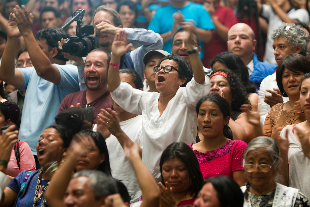 . People celebrate the judge\'s guilty verdict for Guatemala\'s former dictator Jose Efrain Rios Montt during his genocide trial in Guatemala City, Friday, May 10, 2013.  The Guatemalan court convicted Rios Montt on charges of genocide and crimes against humanity, sentencing him to 80 years in prison. The 86-year-old former general is the first former Latin American leader ever found guilty of such a charge. The war between the government and leftist rebels cost more than 200,000 lives and ended in peace accords in 1996. (AP Photo/Moises Castilo)