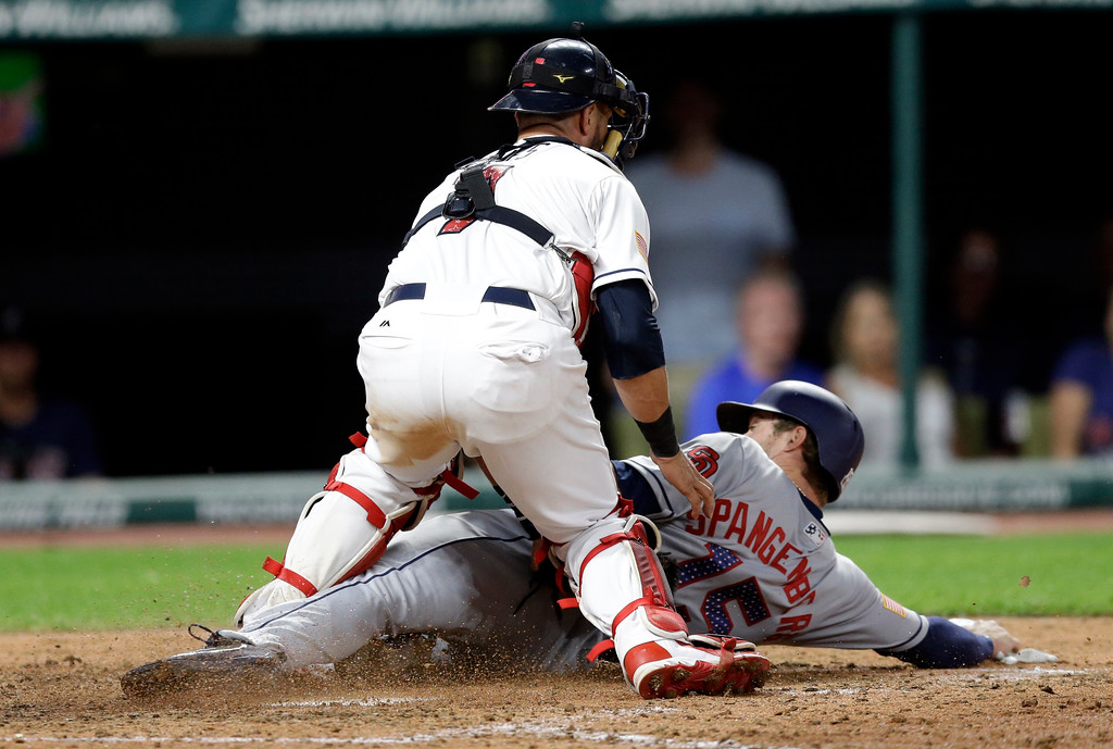 . San Diego Padres\' Cory Spangenberg is tagged out at home plate by Cleveland Indians catcher Yan Gomes in the eighth inning of a baseball game, Tuesday, July 4, 2017, in Cleveland. (AP Photo/Tony Dejak)