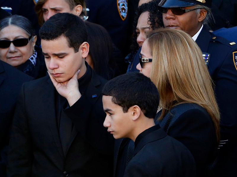 . Justin Ramos, the son of slain New York City police officer Rafael Ramos, left, is comforted by his mother, Maritza Ramos, following funeral services at Christ Tabernacle Church, in the Glendale section of Queens, Saturday, Dec. 27, 2014, in New York. Ramos and his partner, officer Wenjian Liu, were killed Dec. 20 as they sat in their patrol car on a Brooklyn street. The shooter, Ismaaiyl Brinsley, later killed himself. Also pictures is officer Ramos\' other son, Jaden Ramos, bottom. (AP Photo/Julio Cortez)