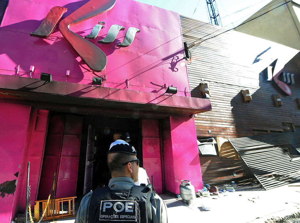 . A policeman checks the Kiss nightclub where a blaze on the eve killed more than 230 people, on January 28, 2013, in Santa Maria, southern Brazil. Brazilian police arrested four suspects --two of the Kiss club\'s owners, along with a pair of musicians who starred in the ill-fated pyrotechnic show, in the wake of the nightclub fire that forced sports officials to defend preparations for the World Cup and Olympics.  ANTONIO SCORZAANTONIO SCORZA/AFP/Getty Images
