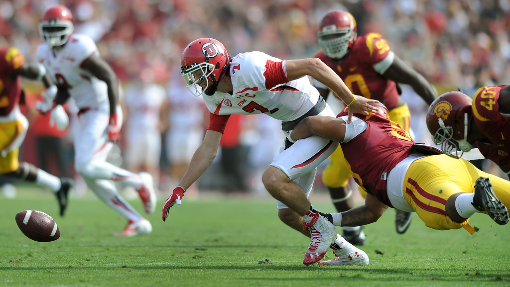 . Utah QB Travis Wilson fumbles the ball as he is hit by USC\'s Antwaun Woods, Saturday, October 26, 2013, at the L.A. Memorial Coliseum. The Trojans recovered the fumble. (Michael Owen Baker/L.A. Daily News)