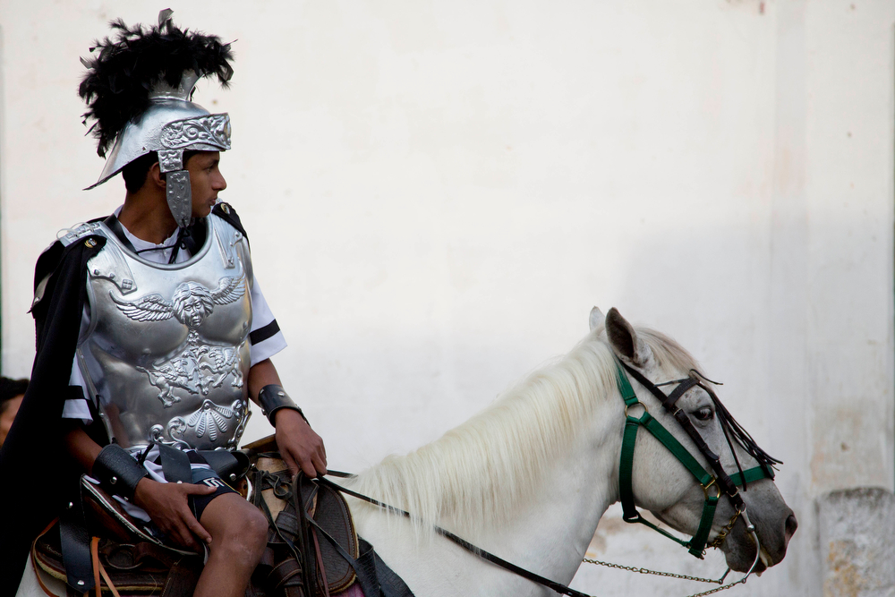 . A man dressed as a Roman soldier rides on a horse during a procession of La Merced church as part of Holy Week celebrations in Antigua Guatemala, Friday, April 18, 2014. This colonial Central American town begins to resemble Biblical Jerusalem with dozens of processions that recreate the final days of Jesus Christ on Earth. Escorting Jesus, hundreds of costumed Roman soldiers roam the streets on foot and on horseback. (AP Photo/Moises Castillo)