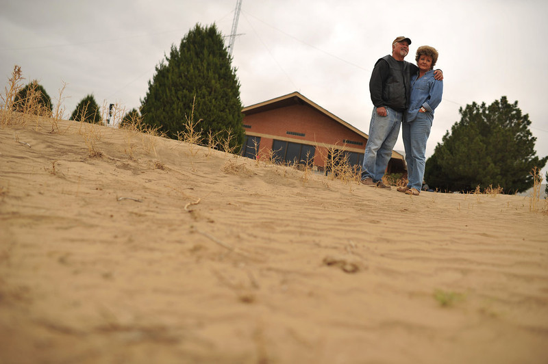 . David Tzilkowski, left, and his wife Jillane Hixson in their backyard in Lamar, Colorado on June 5, 2013. Their farm has been hit by seven different dust storms since last November with a recent storm leaving behind dust drifts as high as three feet in some areas.  (Photo By Hyoung Chang/The Denver Post)
