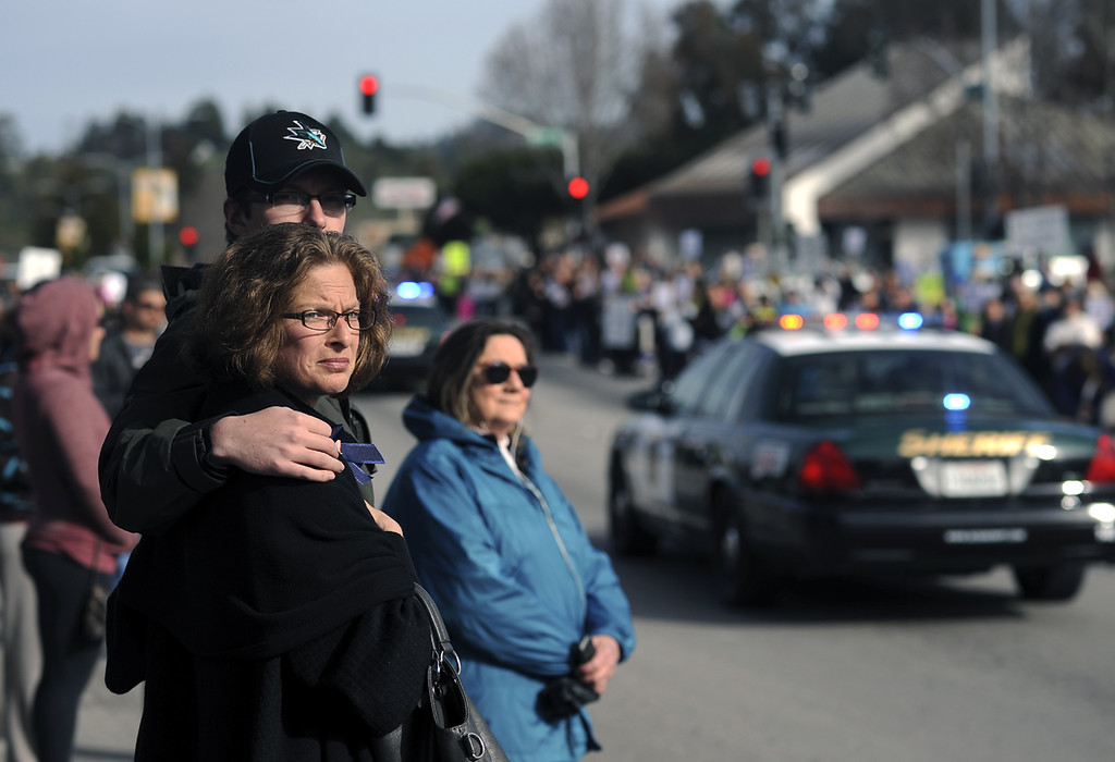 . Santa Cruz residents come to watch the funeral procession for detectives Sgt. Loran \'Butch\' Baker and Elizabeth Butler look down Ocean Street as nearly 200 squad cars make their way toward Highway 17 North en route to HP Pavilion in San Jose, Calif., for memorial services. (Matthew Hintz/Sentinel).