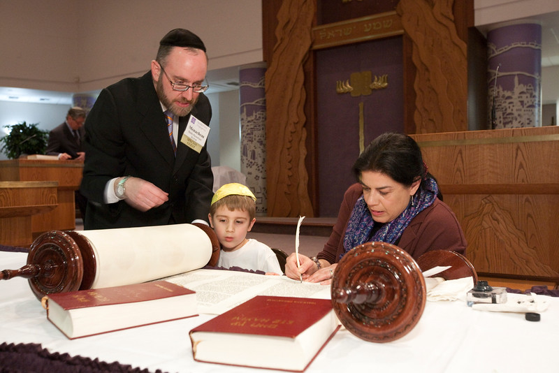 Siyyum Co-Chair Libby Anne Russler fills in the second-to-last letter, while her son Isaac and Rabbi Youlus look on