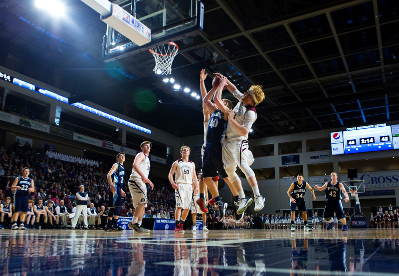 BANGOR, Maine -- 02/18/2017 -- Orono's Jackson Coutts (right) blocks a shot from Presque Isle's Bradley R. Kinney during their Class B boys basketball quarterfinal game at the Cross Insurance Center in Bangor Saturday. Ashley L. Conti   BDN