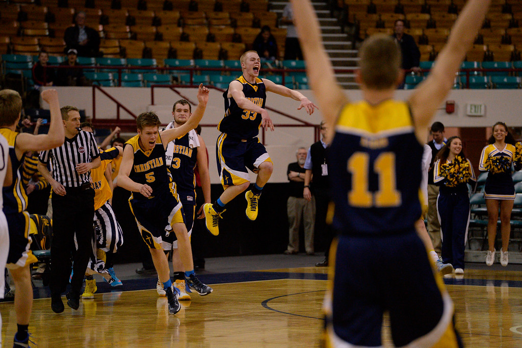 . CS Christian Lions Justin Engesser (33) jumps high int he air to celebrate their championship win over Alamos Mean Moose during the 3A Championship game at the Coliseum. Christian defeated Alamosa 57-43 for the title. (Photo By John Leyba/The Denver Post)