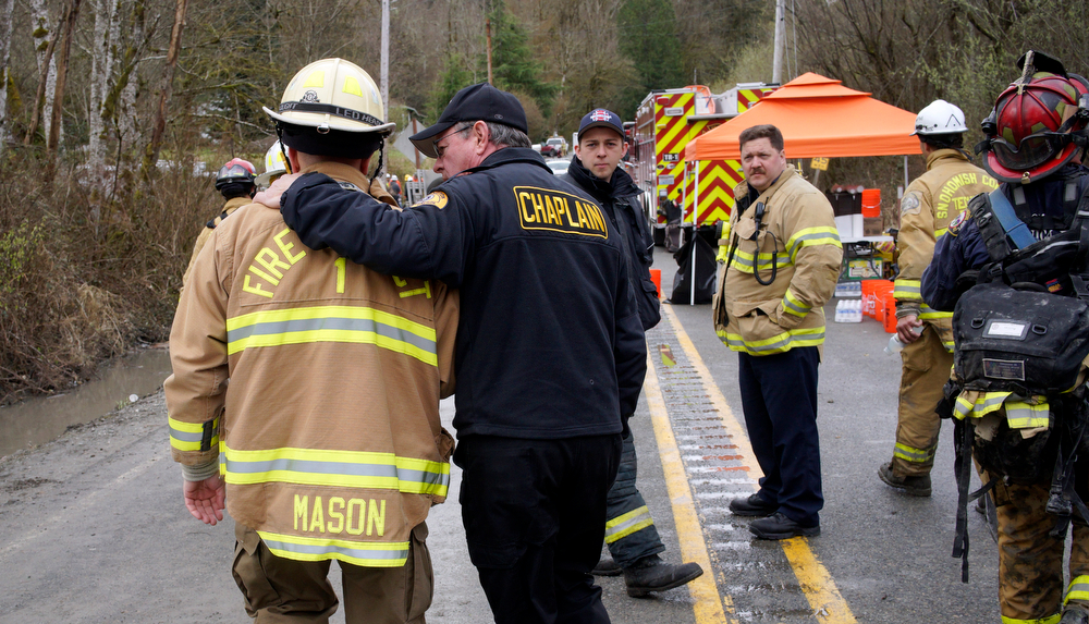 . A chaplain from the Washington State Patrol, right, walks with his arm around Snohomish County battalion chief Steve Mason near the scene of a deadly mudslide, Wednesday, March 26, 2014, in Oso, Wash. Sixteen bodies have been recovered, but authorities believe at least 24 people were killed. And scores of others are still unaccounted for, although many of those names were believed to be duplicates or people who escaped safely. (AP Photo/Rick Wilking, Pool)