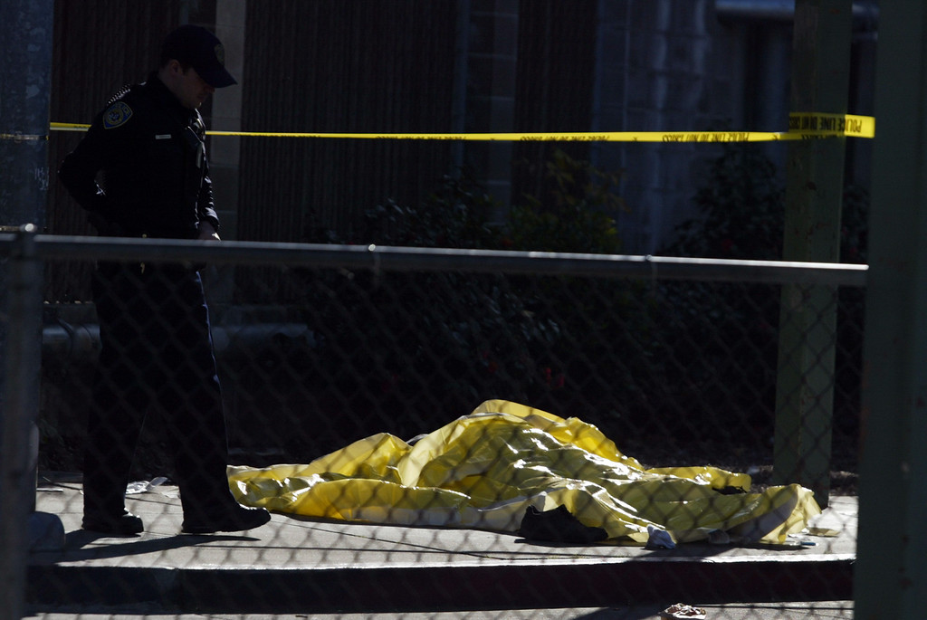 . A dead body lies on the sidewalk next to an AC Transit bus as police investigate the fatal shooting in the bus yard outside the Bay Fair BART station in San Leandro, Calif., on Saturday, Jan. 19, 2013. (Ray Chavez/Staff)