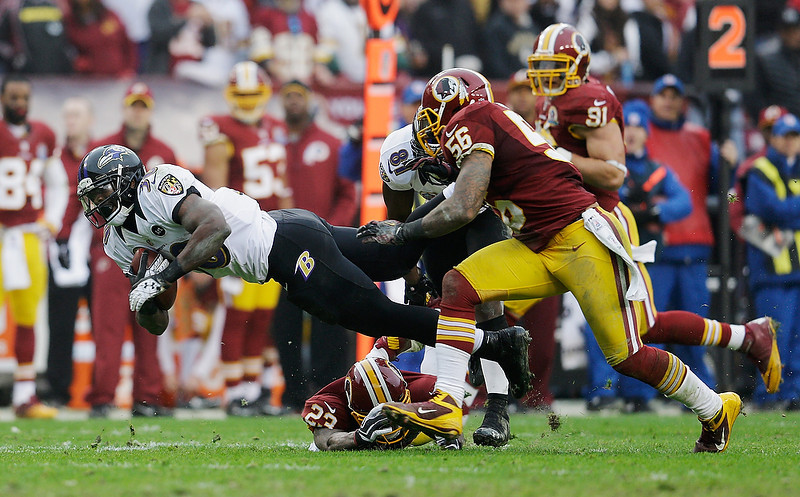 . LANDOVER, MD - DECEMBER 09: Running back Bernard Pierce #30 of the Baltimore Ravens is tackled by DeAngelo Hall #23 and inside linebacker Perry Riley #56 of the Washington Redskins during the third quarter at FedExField on December 9, 2012 in Landover, Maryland.  (Photo by Rob Carr/Getty Images)