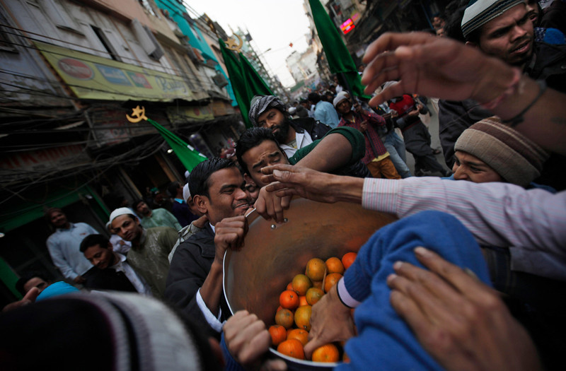 . Indian Muslims jostle to receive free oranges distributed during a procession to mark the birth anniversary of Prophet Muhammad in New Delhi, India, Tuesday, Jan. 14, 2014. (AP Photo/Altaf Qadri)