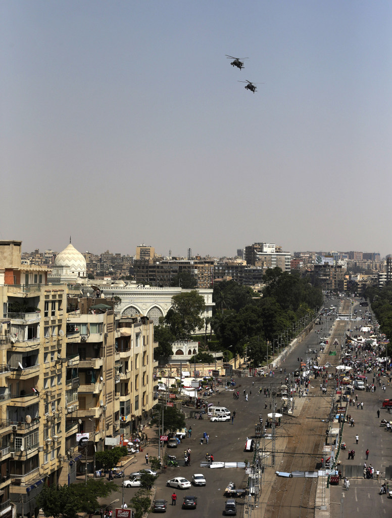 . Military helicopters fly over the presidential palace, in Cairo, Egypt, Tuesday, July 2, 2013.  (Associated Press: Hassan Ammar)