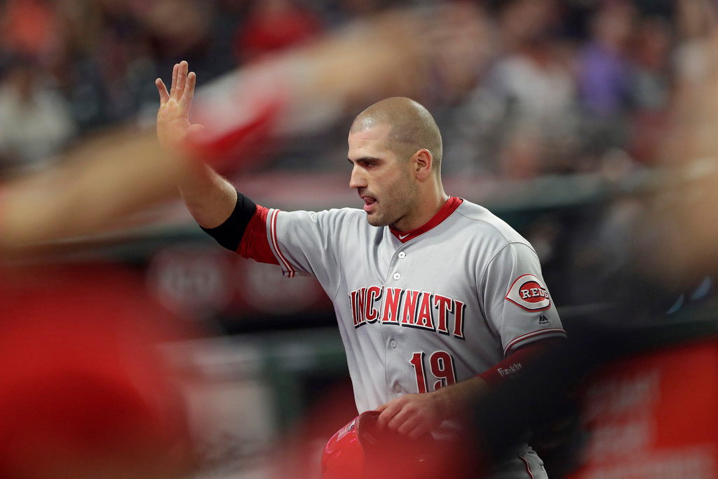 . Cincinnati Reds\' Joey Votto is congratulated by teammates after scoring in the ninth inning of a baseball game against the Cleveland Indians, Tuesday, July 10, 2018, in Cleveland. (AP Photo/Tony Dejak)