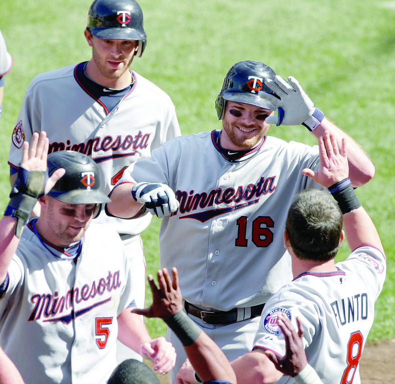 . Minnesota\'s Jason Kubel (16) is congratulated by teammate Nick Punto (8) while returning to the dugout after hitting an eighth-inning grand slam against New York at Yankee Stadium in New York on May 16, 2010. Twins\' Michael Cuddyer (5) and Drew Butera, top, also scored on the play. (AP Photo/Peter Morgan)