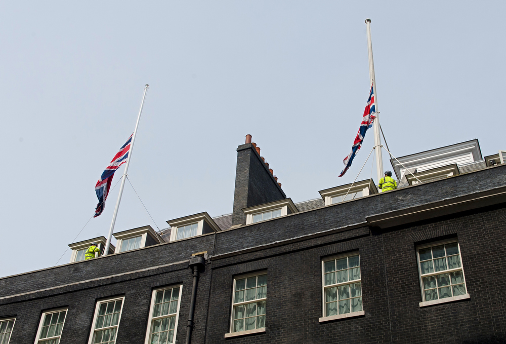 ". Workmen lower Britain\'s Union flags to half-mast above 10 Downing Street in London, on April 8, 2013, following the death of former British Prime Minister Margaret Thatcher. Margaret Thatcher, the ""Iron Lady\"" who shaped a generation of British politics, died following a stroke on Monday at the age of 87, her spokesman said.  LEON NEAL/AFP/Getty Images"
