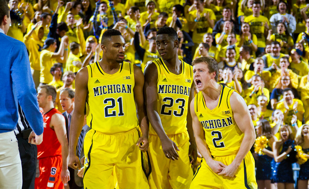 . Michigan guard Spike Albrecht (2) celebrates with teammates Zak Irvin, and Caris LeVert during a timeout in the second half of an NCAA college basketball game at Crisler Center in Ann Arbor, Mich., Tuesday, Dec. 2, 2014. Michigan won 68-65. (AP Photo/Tony Ding)