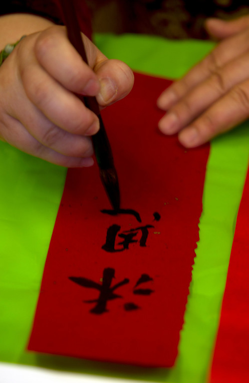. Calligrapher Aiquin Zhou of El Cerrito, Calif. transliterates Grace Naclerio of Alameda, Calif.\'s name into Chinese characters, during the Oakland Museum of California\'s Lunar New Year celebration, Sunday, Feb. 17, 2013 in Oakland, Calif. (D. Ross Cameron/Staff)