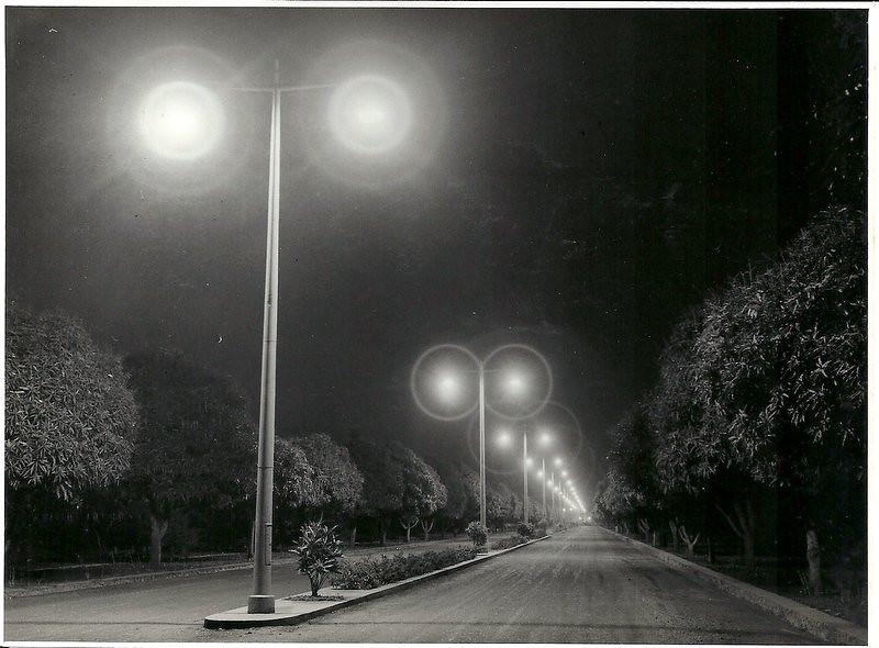"""Avenida do Obelisco Inauguração da iluminação pública, que veio substituir o """"prato"""" com uma lampada que geralmente havia em cada cruzamento. As ruas ainda não estavam alcatroadas."""