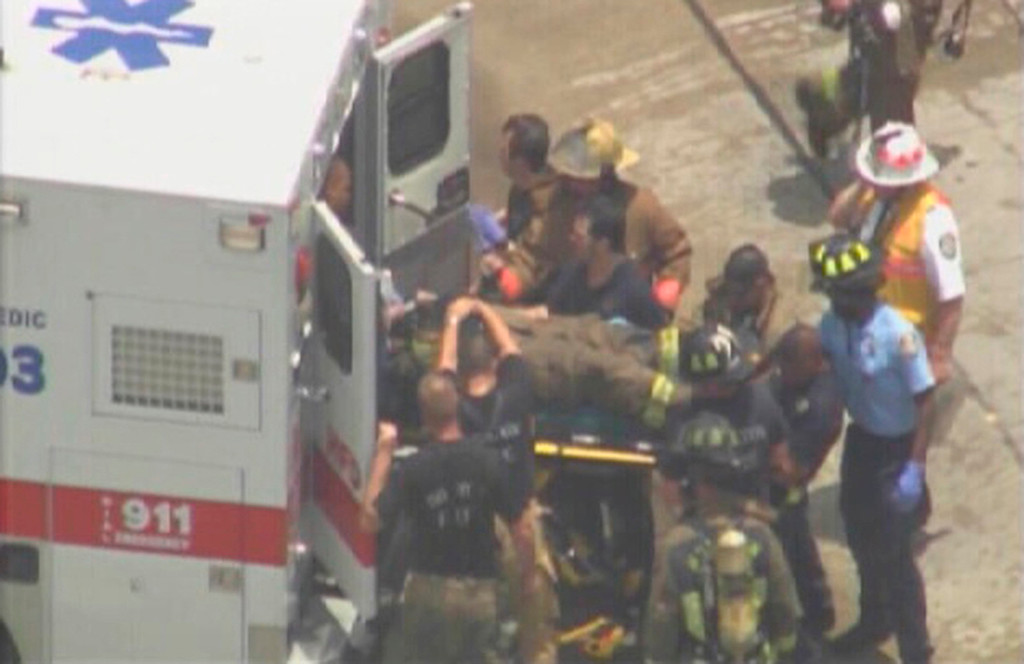 . Firefighters help another firefighter injured in a five-alarm fire at a hotel in southwest Houston, Texas, May 31, 2013 in this image taken from video courtesy of KPRC-Local2. At least six firefighters were injured, two of them very critically, battling a five-alarm fire at a restaurant and hotel in southwest Houston Friday afternoon, the Houston Fire Department said. REUTERS/KPRC-Local2/Handout via Reuters