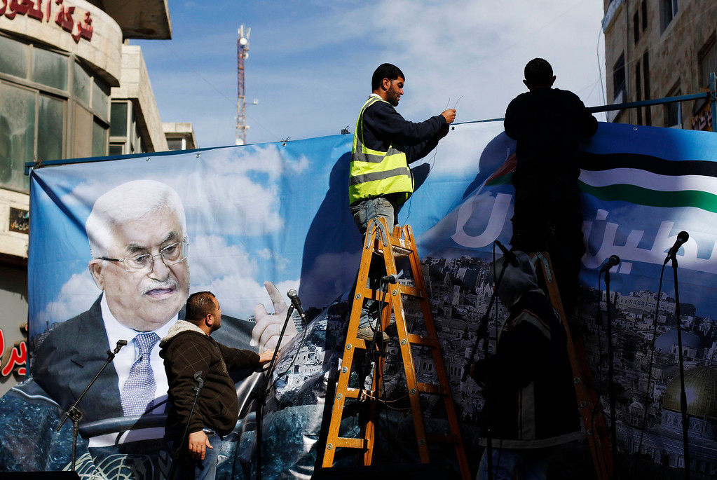 ". Labourers put up a banner depicting Palestinian President Mahmoud Abbas before a rally in the West Bank city of Ramallah, supporting the resolution that would change the Palestinian Authority\'s United Nations observer status from ""entity\"" to \""non-member state,\"" November 29, 2012. The U.N. General Assembly is set to implicitly recognize a sovereign state of Palestine on Thursday despite threats by the United States and Israel to punish the Palestinian Authority by withholding much-needed funds for the West Bank government.  REUTERS/Mohamad Torokman"
