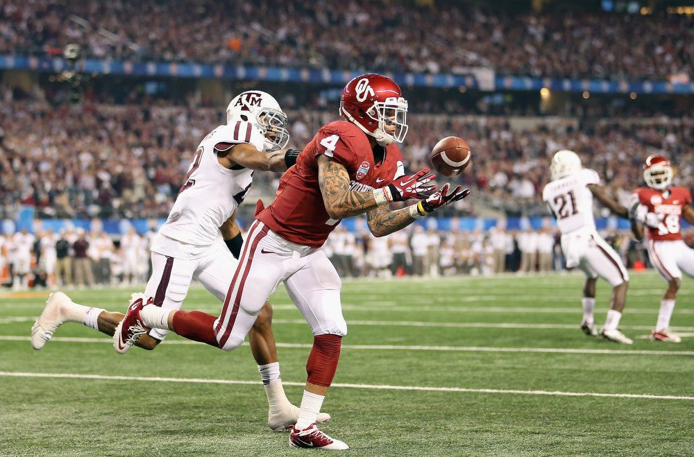 Description of . Kenny Stills #4 of the Oklahoma Sooners drops a pass against Dustin Harris #22 of the Texas A&M Aggies during the Cotton Bowl at Cowboys Stadium on January 4, 2013 in Arlington, Texas.  (Photo by Ronald Martinez/Getty Images)
