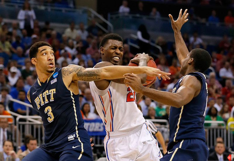 . Casey Prather #24 of the Florida Gators drives and is fouled against Cameron Wright #3 and Michael Young #2 of the Pittsburgh Panthers in the second half during the third round of the 2014 NCAA Men\'s Basketball Tournament at Amway Center on March 22, 2014 in Orlando, Florida.  (Photo by Kevin C. Cox/Getty Images)