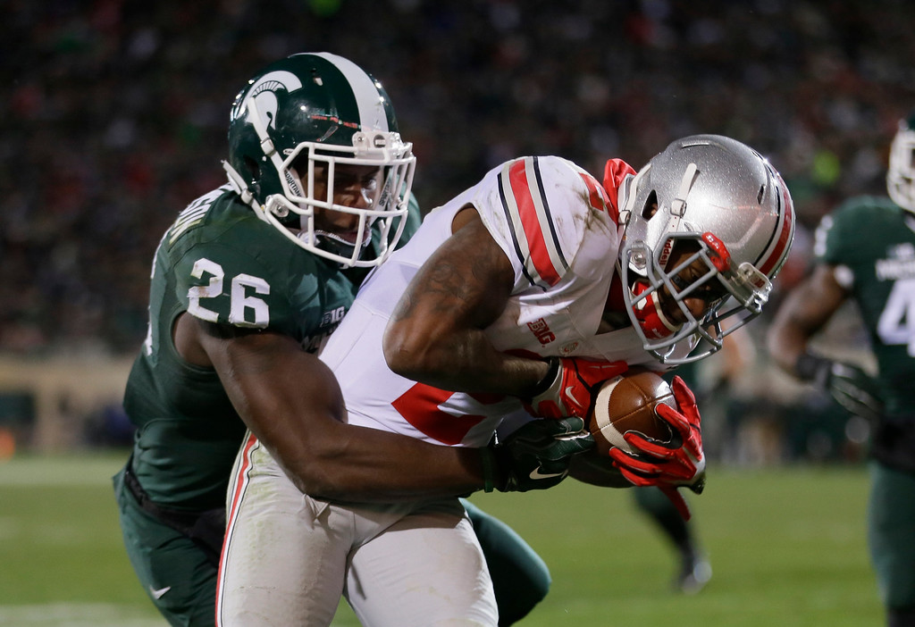 . Ohio State running back Dontre Wilson, defended by Michigan State safety RJ Williamson (26), scores on a 7-yard reception during the second half of an NCAA college football game in East Lansing, Mich., Saturday, Nov. 8, 2014. Ohio State won 49-37.  (AP Photo/Carlos Osorio)