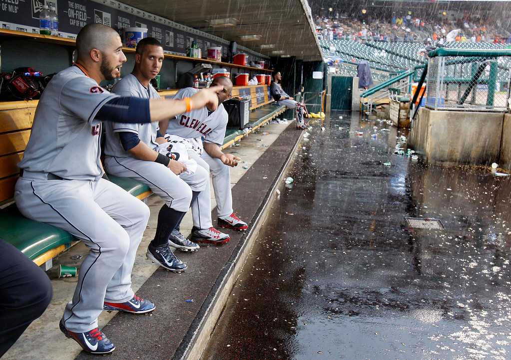. Cleveland Indians\' Mike Aviles, from left, Michael Brantley and Michael Bourn sit in the dugout during a rain delay of a baseball game against the Detroit Tigers, Sunday, June 14, 2015, in Detroit. (AP Photo/Duane Burleson)