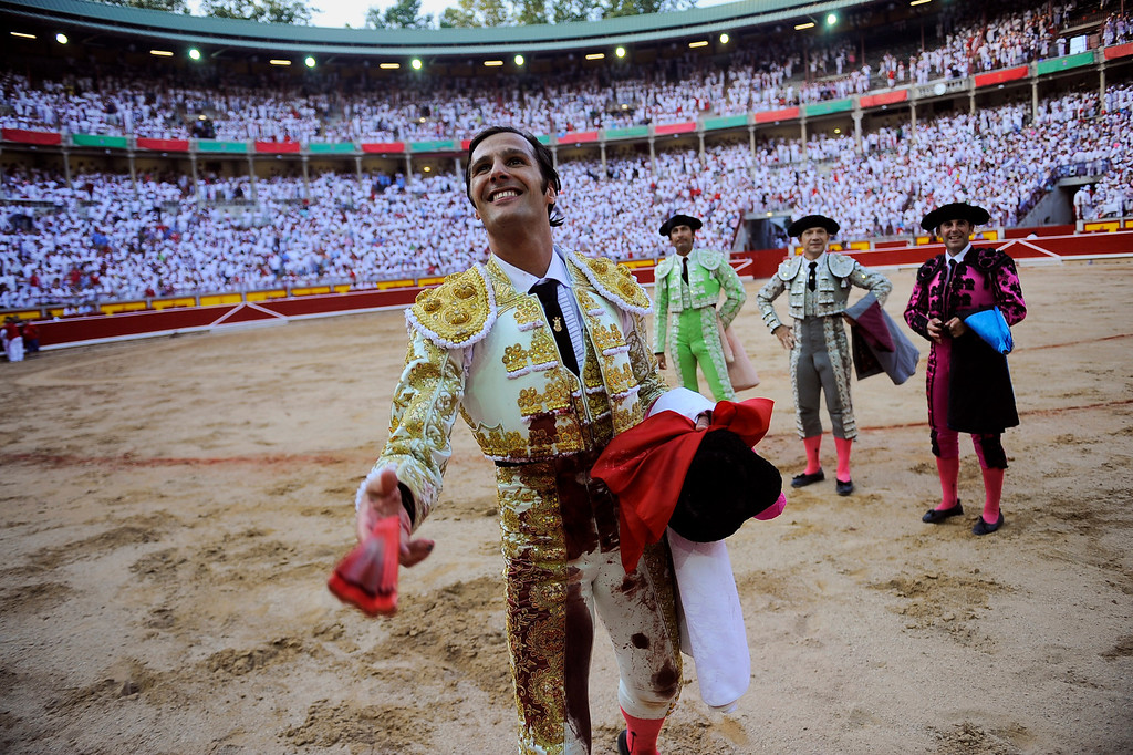 . Spanish bullfighter David Mora is congratulated at the end of bullfight, at the San Fermin fiestas, in Pamplona northern Spain on Thursday, July 11, 2013. (AP Photo/Alvaro Barrientos)