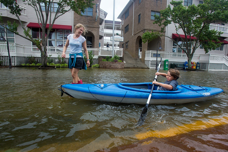 . Lauren Heesemann, left, smiles at her nephew Summit Gibson, 7, from Oklahoma as he tries to maintain his balance on the kayak through a flooded street on Friday, July 4, 2014, in Manteo, N.C. The storm was expected to bring a lousy July Fourth beach day with it as it moved offshore of the northeast coast. Forecasters did predict a second landfall Saturday evening in New Brunswick and Nova Scotia in Canada. (AP Photo/The Virginian-Pilot, Hyunsoo Leo Kim)