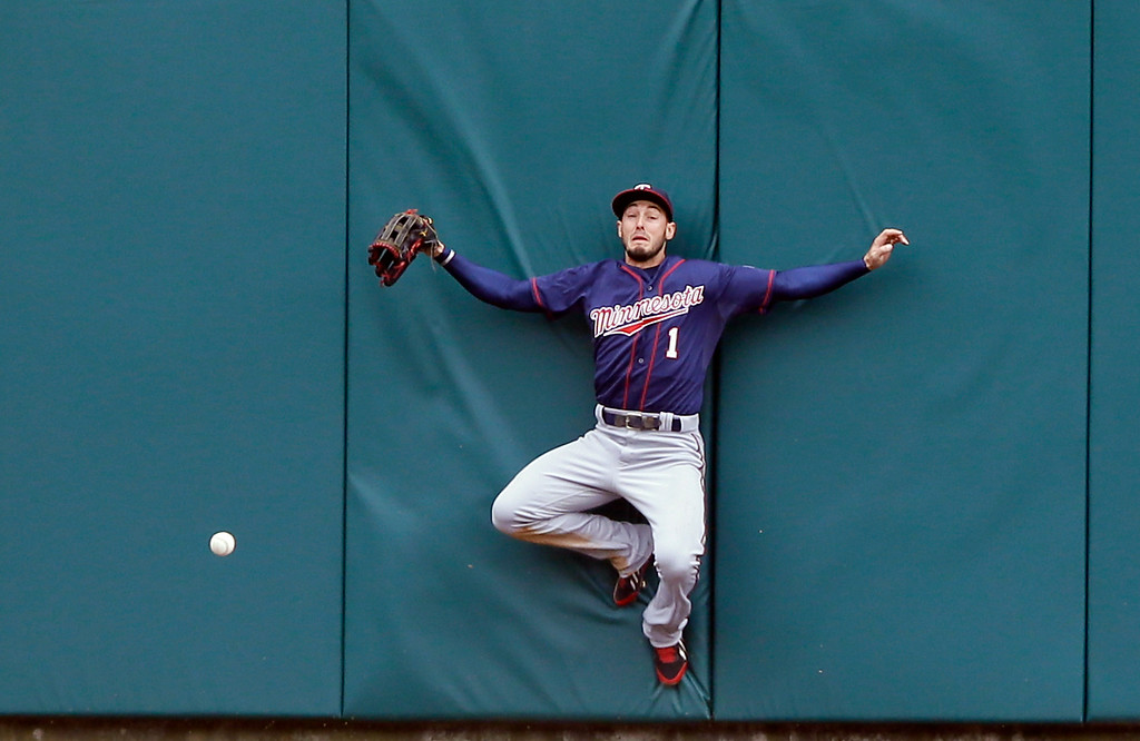 . Minnesota Twins center fielder Jordan Schafer misplays the triple hit by Detroit Tigers\' Yoenis Cespedes during the sixth inning of an opening day baseball game in Detroit, Monday, April 6, 2015. (AP Photo/Carlos Osorio)