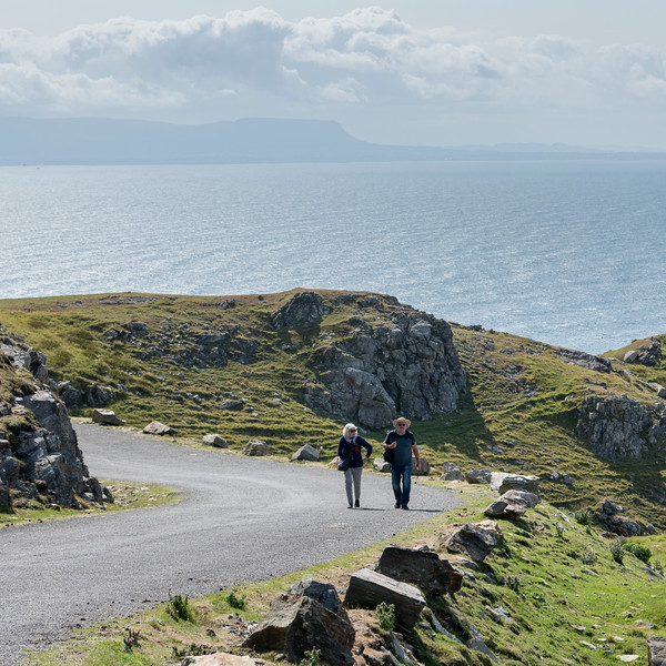 Couple walking along roadway off the Slieve League, County Donegal, Ireland